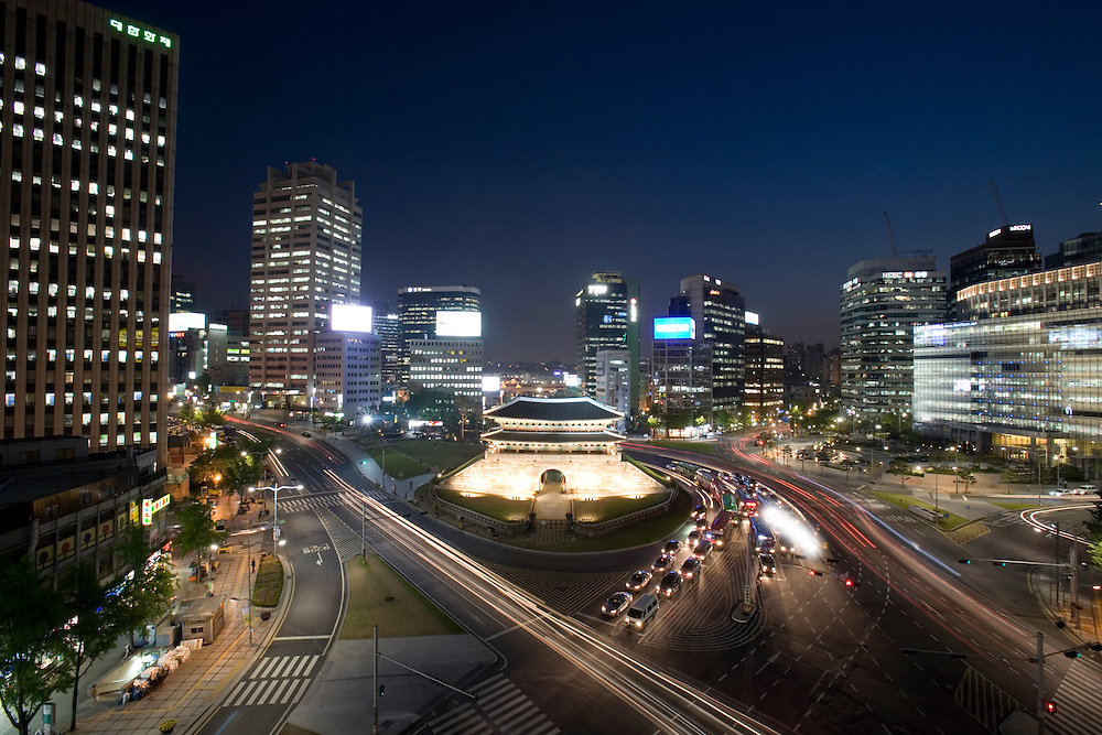 South Korea, Seoul, Traffic circles Namdaemun (Great South Gate) surrounded by modern office buildings of the city skyline at dusk