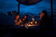 Kemen(L), Nathalie (C) and Beñat talk to each other after they had dinner. Village of Brontallo (Switzerland) July 05, 2014. Beñat and Nathalie spend two months (July and August) on Spulüi, at 1.900 meters, taking care of goats and making cheese. Their children Kemen (7 years old) and Oihu (18 months) are with them. (Gari Garaialde / Bostok Photo)