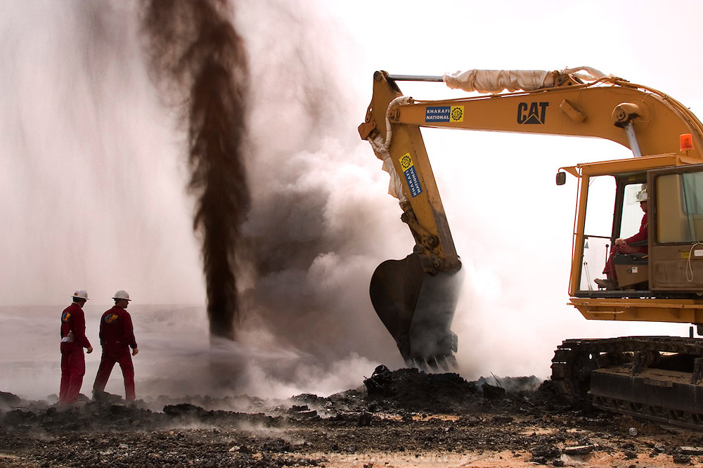 "Boots and Coots team members direct a backhoe clearing debris away from a gushing oil well minutes after the fire was extinguished (the ground is still smoking). The well was capped two hours later using a ""stinger,"" a tapered pipe on the end of a long steel boom controlled by a bulldozer. Drilling mud, under high pressure, was pumped through the ""stinger"" into the well, stopping the flow of oil and gas. Many of the wells are 10,000 feet deep and produce huge volumes of oil and gas under tremendous pressure, which makes capping them very difficult and dangerous. Rumaila is also spelled Rumeilah."