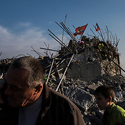 A father and son wander through the rubble of a WWII memorial complex near the Russian border, in Snizhne.