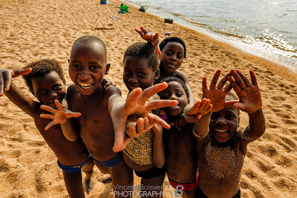 a group of kids looking to the camera and laying hands while laughting, Cape Maclear, malawi