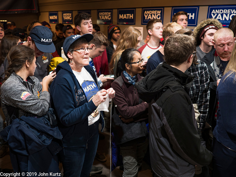 12 DECEMBER 2019 - DES MOINES, IOWA: A woman in the crowd knits while people wait for Andrew Yang at the opening of his office in Ames, IA. Yang, an entrepreneur, is running for the Democratic nomination for the US Presidency in 2020. He brought bus tour to Ames, IA, Thursday. Iowa hosts the the first election event of the presidential election cycle. The Iowa Caucuses will be on Feb. 3, 2020.        PHOTO BY JACK KURTZ