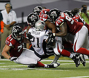 ATLANTA - AUGUST 19:  Running back Fred Taylor #21 of the New England Patriots is tackled by members of the Atlanta Falcons defense during the preseason game at the Georgia Dome on August 19, 2010 in Atlanta, Georgia.  (Photo by Mike Zarrilli/Getty Images)