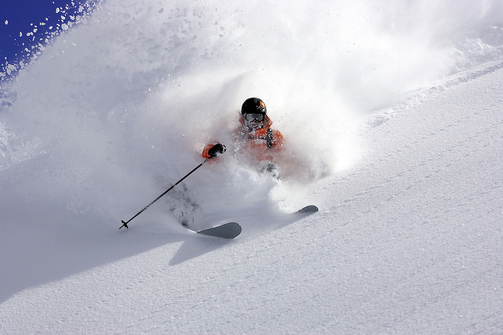 Male skier turning in fresh snow on steep mountainside