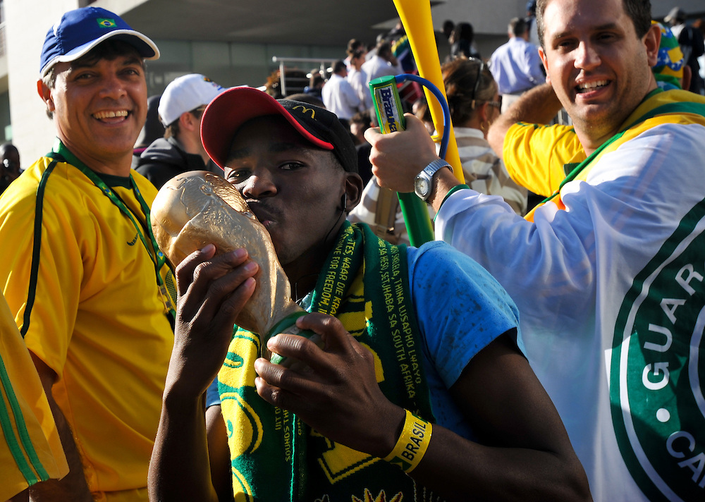 A South Africa fan kisses a replica of the World Cup trophy as he waits in line to buy tickets Tuesday, June 8, 2010 outside a ticketing center in Johannesburg, South Africa. Photo by Bahram Mark Sobhani