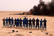 "Firefighters from the Kuwait Oil Company (called KWWK: Kuwait Wild Well Killers) pray at noon by the first oil well fire they were working on in Iraq's Rumaila Oil field. Later in the day they extinguished this smoky fire and the next day stopped the flow of gas and oil with drilling mud using what is called a ""stinger"", (a tapered pipe on the end of a long steel boom controlled by a bulldozer. Drilling mud, under high pressure, is pumped through the stinger into the well, stopping the flow of oil and gas). The Rumaila field is one of Iraq's biggest oil fields with five billion barrels in reserve. The burning wells in the Rumaila Field were ignited by retreating Iraqi troops when the US and UK invasion began in March 2003. Rumaila is also spelled Rumeilah."