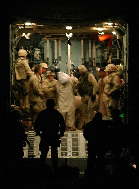 Coalition forces deliver the first al Qaeda detainees  in Kandahar International Airport.  Taliban and al Qaeda detainees are to be brought in before heading for Cuba.