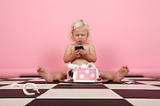 young blonde girl of two sits on a checkered floor, plays with an iPhone Model release available