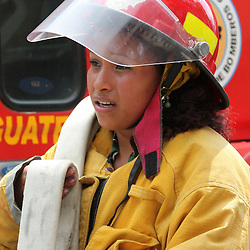 Volunteer woman fire fighter, carries hoses as crews takle a blaze in the historic center of Antigua, Guatemala