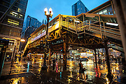 "Rainy night in Chicago on the corner of State and Lake with the ""L"" and Chicago Theater."