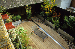 View from top roof terrace to lower decked area with steel rill and metal planters. Water feature cascading from brickwork. Black painted fence. Design: Diarmuid Gavin