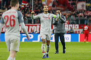 Liverpool defender Virgil van Dijk (4) pumps in his fists in the air towards the travelling Liverpool fans after the Champions League match between Bayern Munich and Liverpool at the Allianz Arena, Munich, Germany, on 13 March 2019.