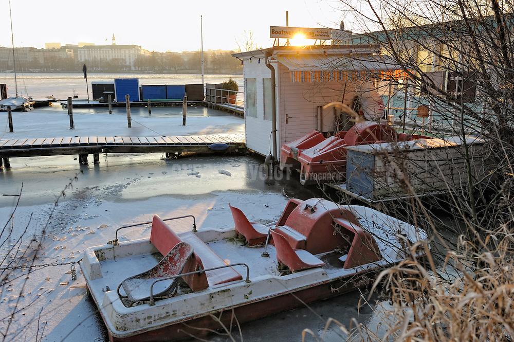 Sonnenaufgang am früher Morgen im Winter an der Alster. Ein festgefrorenes Tretboot liegt am Steg eines Bootsverleih. Im Hintergrund das Hotel Atlantic.