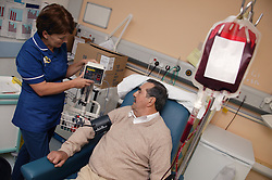 Day Care Manager taking blood pressure whilst Haematology day patient is having a blood transfusion,