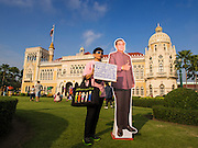 10 JANUARY 2015 - BANGKOK, THAILAND: A woman carrying a pro-government sign, which thanks Gen. Prayuth for stabilizing Thailand, poses with a life sized cardboard cutout of General Prayuth Chan-ocha, the Prime Minister of Thailand during Children's Day festivities at Government House. Prayuth commanded a coup that deposed the elected government in May 2014. National Children's Day falls on the second Saturday of the year. Thai government agencies sponsor child friendly events and the military usually opens army bases to children, who come to play on tanks and artillery pieces. This year Thai Prime Minister General Prayuth Chan-ocha, hosted several events at Government House, the Prime Minister's office.   PHOTO BY JACK KURTZ