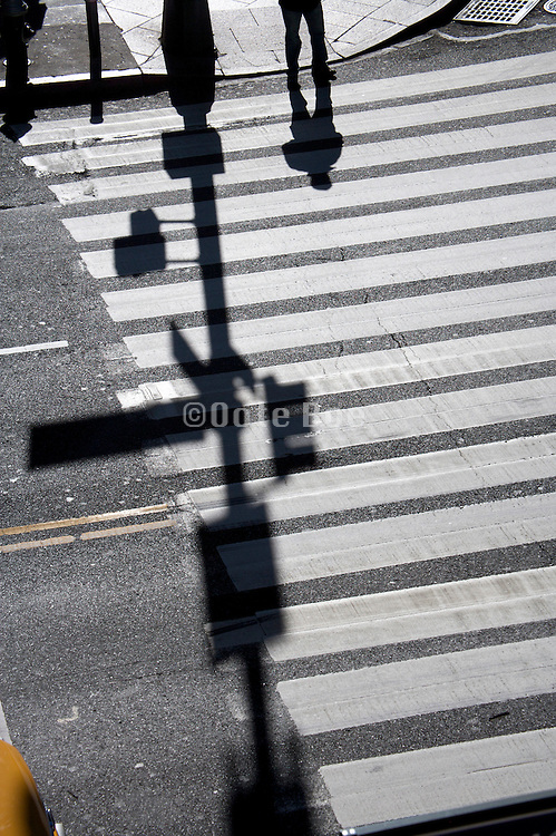 shadow of one person waiting to cross the road
