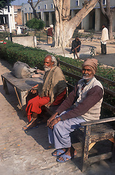 Men with learning disabilities sitting on bench in the grounds of the Apahaj Ashram; Patiala; Punjab; India,