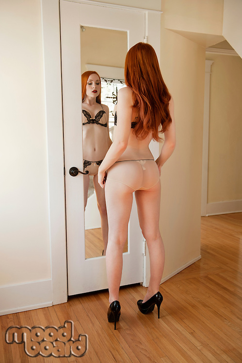 Back view of a young woman in lingerie standing in front of mirror
