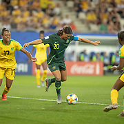 GRENOBLE, FRANCE June 18.  Sam Kerr #20 of Australia scores her third goal as she shoots past Sashana Campbell #12 of Jamaica and Allyson Swaby #17 of Jamaica during the Jamaica V Australia, Group C match at the FIFA Women's World Cup at Stade des Alpes on June 18th 2019 in Grenoble, France. (Photo by Tim Clayton/Corbis via Getty Images)
