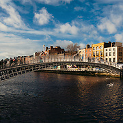Beautiful Sunlight on Dublin's Hapenny Bridge as people walk across it an the warm sunlight reflects on the buildings in the background and the water below
