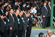 Japan, Hiroshima : HIROSHIMA, JAPAN - AUGUST 06: Japanese Prime Minister Shinzo Abe bows to the crowd during the 70th anniversary ceremony of the atomic bombing of Hiroshima at the Hiroshima Peace Memorial Park on August 6, 2015 in Hiroshima, Japan. Japan marks the 70th anniversary of the first atomic bomb that was dropped by the United States on Hiroshima on August 6, 1945. The bomb instantly killed an estimated 70,000 people and thousands more in coming years from radiation effects. Three days later the United States dropped a second atomic bomb on Nagasaki which ended World War II.