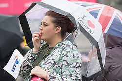 "Trafalgar Square, London, June 12th 2016. Rain greets Londoners and visitors to the capital's Trafalgar Square as the Mayor hosts a Patron's Lunch in celebration of The Queen's 90th birthday. PICTURED: A woman with an ""I love London"" umbrella watches the performers on stage."
