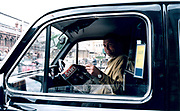 Man sitting in driver's seat of van reading Sun newspaper.