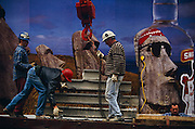 Construction workers wearing hard hats hook up a pile of concrete beams on to a waiting crane hook. One man bends down to help loop a chain beneath one of the girders and attached to the dangling hook while another secures the chain and another man is in radio contact with the crane driver out of sight. Importantly, behind their low-loader truck is a Smirnoff advertising billboard with a famous ad campaign for the Vodka distillery. It depicts three carved Polynesian statues of Easter Island but seen through a botttle of the alcoholic beverage, is a representation of a face wearing a head band and MP3 headphones. Seen juxtaposed with the construction men and their building technology this scene describes a visual pun between an ancient lost civilization and the modern age of technology. Smirnoff is a vodka distillery founded in Moscow, by Piotr Arsenieyevich Smirnov. The .brand is now distributed in 130 countries and includes flavored vodka and malt beverages. The Sminoff advertising campaign is said to be based on the Belgian surrealist artist Rene Magritte whose paradoxical images stretched our ideas of what was reality and the fantastic...