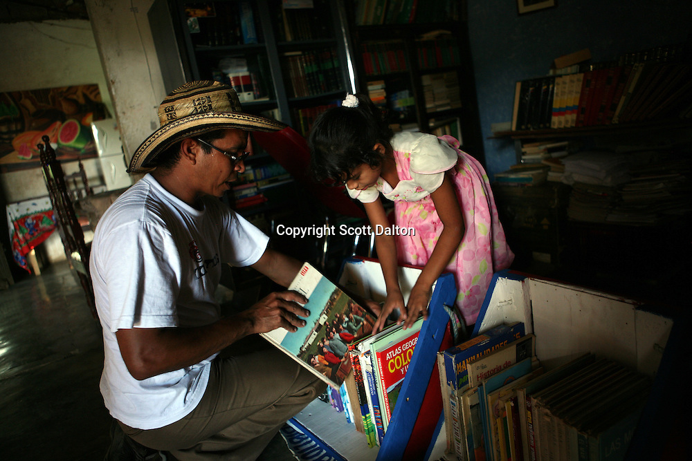 Luis Soriano, 36, and his daughter Susana, 7 years old, prepare books that will be loaded onto his Biblioburro, or Donkey Library, at their home in La Gloria, in northern Colombia on Saturday, October 11, 2008. Mr. Soriano regularly takes long treks with his donkeys in tow in order to bring books to rural communities. (Photo/Scott Dalton)