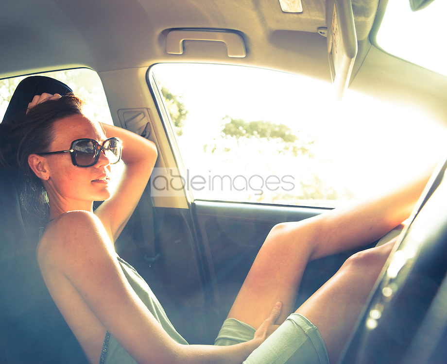 Woman Reclining in Car with Legs Raised