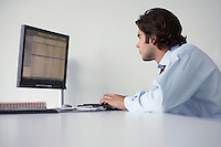 Business man using computer side view