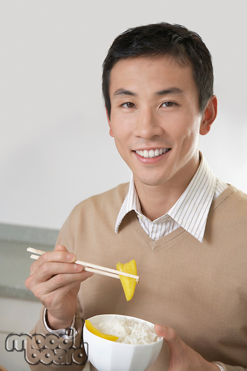 Young Man Eating Rice and Peppers with chopsticks