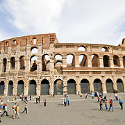 A wide-angle shot of Rome's famous and historic Coliseum during the daytime, with tourists around the piazza.