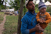 Young Roma father, carrying his son, in the yard of their home in the village of Dimacheni in Botosani County, Romania. He has previously worked in the building industry in Italy and now he and his wife are in the process of repairing their newly-bought home in the traditionally Romanian (non-Roma) section of the village.