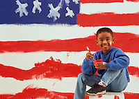 Boy (6-8) painting American flag on wall