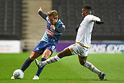 Milton Keynes Dons striker Kieran Agard (14) comes in to tackle Wycombe Wanderers midfielder Alex Pattison (8) during the EFL Trophy match between Milton Keynes Dons and Wycombe Wanderers at stadium:mk, Milton Keynes, England on 12 November 2019.