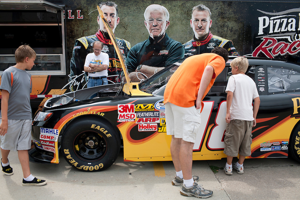 People look at Joe Gibbs Racing's no. 18 car before a campaign appearance by Republican presidential hopeful Michele Bachmann campaigns on Friday, August 5, 2011 in Newton, IA.