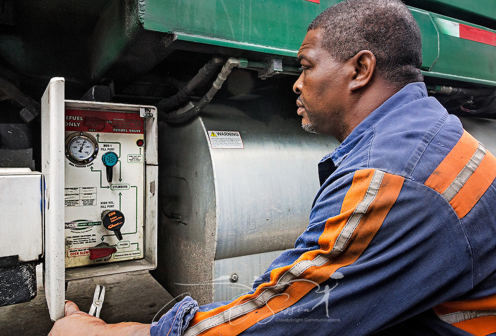"Diesel mechanic Lawrence Henderson checks the control panel of a CNG-powered (compressed natural gas) Mack Truck at Waste Pro, March 19, 2016, in Jacksonville, Florida. Waste Pro offers waste and recycling services to more than two million residential customers and more than 40,000 businesses in Alabama, Florida, Georgia, South and North Carolina, Louisiana, Mississippi, and Tennessee. The company has committed to ""going green"" by implementing a number of green initiatives, including using CNG (Clean Natural Gas) in its trucks, recycling more waste instead of sending it to landfills, and powering its regional headquarters throuh solar energy. (Photo by Carmen K. Sisson/Cloudybright)"