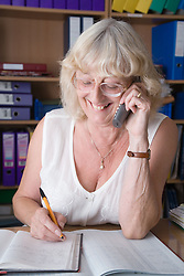 Woman making an appointment in diary whilst on the telephone,