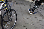 A person carries a bicycle wheel, minus its tyre, past locked up bikes in central London.