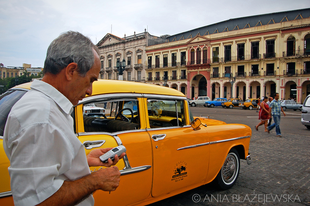 Cuba, Havana. Yellow taxi and its driver with a mobile phone.