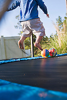 Child age 3 plays on a trampoline