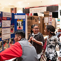 Left to right, Johnson Phillips, the Navajo Nation Science Fair Coordinator judges a project by 4th grade Ch'ooshgai Community School students Hayden Skeet, 9, and Nazhea Brown, 9, on the first day of the Navajo Nation Science Fair, Tuesday, Feb. 26 in Church Rock, NM.