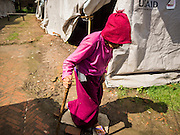 02 AUGUST 2015 - BHAKTAPUR, NEPAL:  An elderly woman walks through a small Internal Displaced Person (IDP) camp at Durbar Square in Bhaktapur for people left homeless by the Nepal earthquake. The Nepal Earthquake on April 25, 2015, (also known as the Gorkha earthquake) killed more than 9,000 people and injured more than 23,000. It had a magnitude of 7.8. The epicenter was east of the district of Lamjung, and its hypocenter was at a depth of approximately 15km (9.3mi). It was the worst natural disaster to strike Nepal since the 1934 Nepal–Bihar earthquake. The earthquake triggered an avalanche on Mount Everest, killing at least 19. The earthquake also set off an avalanche in the Langtang valley, where 250 people were reported missing. Hundreds of thousands of people were made homeless with entire villages flattened across many districts of the country. Centuries-old buildings were destroyed at UNESCO World Heritage sites in the Kathmandu Valley, including some at the Kathmandu Durbar Square, the Patan Durbar Squar, the Bhaktapur Durbar Square, the Changu Narayan Temple and the Swayambhunath Stupa. Geophysicists and other experts had warned for decades that Nepal was vulnerable to a deadly earthquake, particularly because of its geology, urbanization, and architecture.      PHOTO BY JACK KURTZ