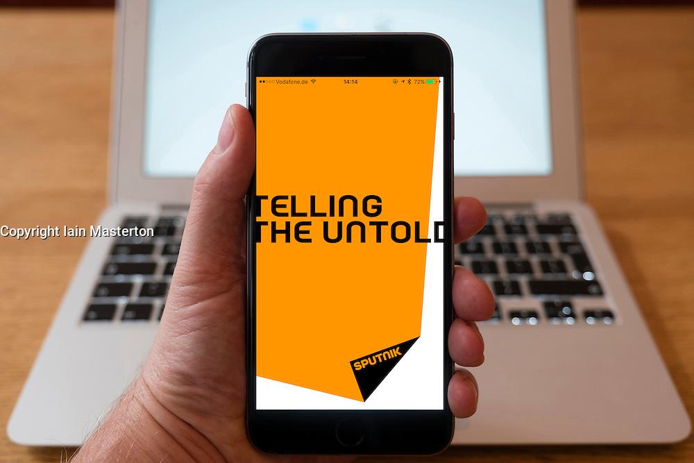 Using iPhone smartphone to display homepage of Sputnik Russian , English language, news propaganda media outlet