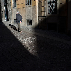 Bergamo, Italy - A man walks in the historical centre of Upper Bergamo (Bergamo Alta) at sunset