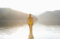 Woman in yellow bikini stands at edge of lake