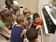 Teacher Shandra Sarasio Meyer (from left) talks with Laela Waddell, 10 of Wellman, Jesse Dalley, 9, of Council Bluffs, Quentin Strohm, 10, of Ames, Peyton Tshilumba 8, of Kalona, and Noah Fink, 10, of Waverly, as they watch their shrinky dinks in the oven during a summer camp hosted by the Iowa School for the Deaf at the Iowa Braille and Sight Saving School in Vinton on Tuesday, July 16, 2013. Sarasio Meyer is a teacher with Area Educational Agency 267 in Forest City.