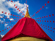 18 NOVEMBER 2015 - BANGKOK, THAILAND:  A red cloth is dropped over the chedi at Wat Saket marking the start of the temple's annual fair. Wat Saket is on a man-made hill in the historic section of Bangkok. The temple has golden spire that is 260 feet high which was the highest point in Bangkok for more than 100 years. The temple construction began in the 1800s in the reign of King Rama III and was completed in the reign of King Rama IV. The annual temple fair is held on the 12th lunar month, for nine days around the November full moon. During the fair a red cloth (reminiscent of a monk's robe) is placed around the Golden Mount while the temple grounds hosts Thai traditional theatre, food stalls and traditional shows.     PHOTO BY JACK KURTZ