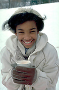 Happy girl age 11 holding cup of cocoa at winter snow sledding.  St Paul  Minnesota USA
